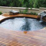 swimming pool wood deck rocks waterfall plants