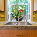 tropical garden windows for kitchens with beautiful flowers planted on a black pot above steel kitchen sink and amazing countertops plus wooden kitchen cabinets