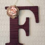 unique F large decorative letter design made of wood with brown color with flower accent in pink color on white wall