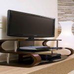 unique shaped idea tv stand in double s shape with brown glossy base on wooden floor aside artistic white ceramic
