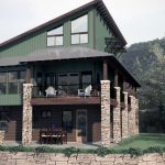 Unique Two Story Small Lake House Design With Stone Beams And Green Siding And Open Plan