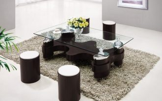 urban style living space idea with unique glass coffee table and black round stools on gray furry rug in spacious room