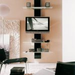 vertical shaped storage idea for tv stand beneath cream wall with floor mirror and black seating