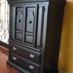vintage wooden black tall dresser design beneath yellow wall on wooden floor with carved surface