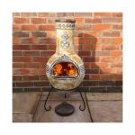 vintage yellow painted chiminea fire pit design with metal scrolled legs aside red brick wall on concrete patio