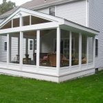 white glassed in porch wicker furniture green grass yard decorative flower in pot white vinyl home siding