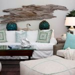 white slipcovered sofa for coastal living room decorated with decorative cushion and wooden coffee table with glass top and armchair plus stool and end table
