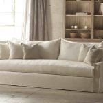white slipcovered sofa with cushions and wooden cabinets behind the sofa and drapes plus vintage wall mounted