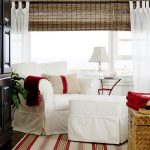 white slipcovered sofa with red accent on its cushions and striped rug and footstool plus storage and shades plus drapes and table lamp