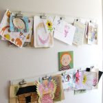 white wall with pictures and painting and paper clip for displaying kids art