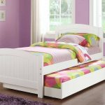 white wooden trundle beds for children with colorful bedding set and hardwood flooring plus purple wall paint scheme and purple rug plus white curtain
