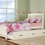 white wooden trundle beds for children with pink purple bedding set and storage underneath plus floral rug and soft wall paint and twin beds