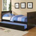 wooden trundle beds for children with stiped bedding set and beige rug plus dart game and pictures on wall  decoration and wooden laminate floor