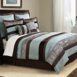 A bed frame with higher black headboard and teal plus brown bedding and pillows black painted wood bedside table with drawer system underneath white knitted wool rug
