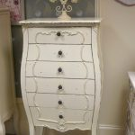 A drawer system in white which is designed in French style a small decorative oval mirror with floral themed frame