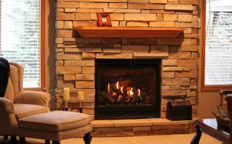 A fireplace with natural stone wall system and wood shelf over the firebox a cozy corner chair with ottoman table