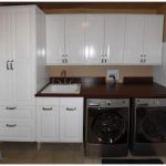 A laundry room cabinet system consisting tall cabinet wall cabinet series and under cabinets plus drawer system a dark wood countertop with white sink and faucet modern washer machine