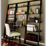 A leaning ladder bookshelf with desk in the center and white cushioned chair