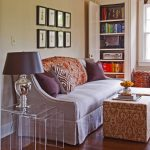 A living room consists of couch and colorful throw pillows an ottoman table  built in bookcases an arrangement of picture frames hang on the wall three pieces of clear nesting side table