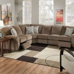 A microfiber recliner in sectional design some decorative pillows modern rug a darker brown coated wood side table with picture frame and table lamp