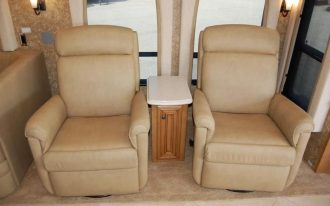 A pair of light cream recliner for outdoor a small wood side table with white marble top