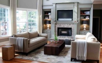 A pair of light cream sofas with back cushions two solid wood side table a darker coated wood table a fireplace building built in TV cabinet with additional storage system