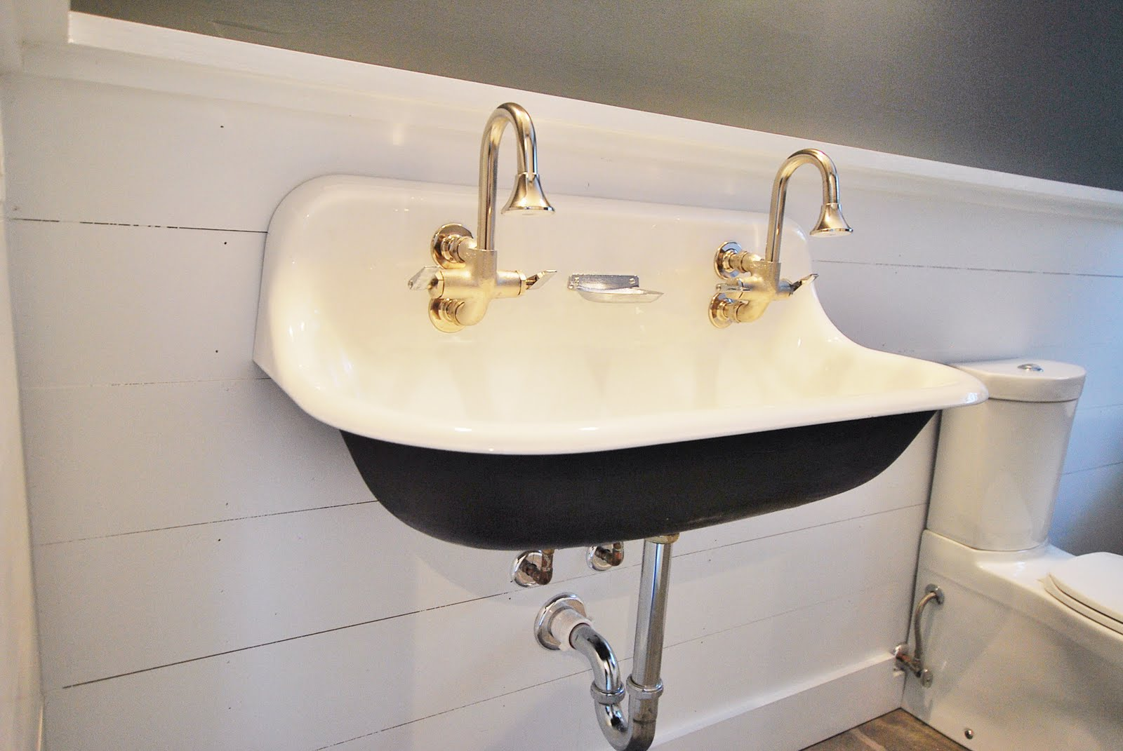 A Small And Deep White Sink With Double Nickel Faucets That Is Mounted On  Wall System