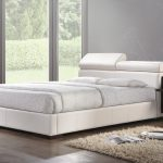A white platform queen bed frame with unique white leather headboard white bed cover with white pillows floating black and white bedside table medium sized white shaggy rug for bedroom
