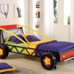 Amazing-Max-Metal-Car-Bed-in-Twin-Size-for-Kids-in-blue-yellow-red-and-green-colors-surrounded-with-white-wall-and-wooden-floor-and-rackets-and-yelloe-flowers