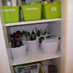 Bathroom cabinet idea with three green storage boxes white plastic storage bowls and yellow storage basket