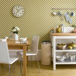 Beautiful polka dots wallpaper for wall and kitchen backsplash in a small kitchen a wooden dining table with white dining chairs a white kitchen counter with wooden top and under shelves unit