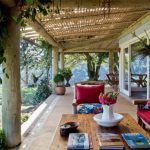Beautiful-terrace-with-natural-wooden-poles-and-canopy-with-green-plants-and-rustic-table-with-chic-centerpiece-red-armchairs-and-red-cushions