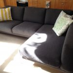 Black Sectional Couch And Light Pillows With Fur Rug