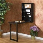 Black coated wooden folding down desk with shelves mounted on wall