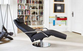 Black leather recliner with headrest and metal armrest a wall bookcase