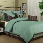 Black stained metal bed frame with black metal headboard and  pretty teal and brown bedding and pillows a black painted wooden bedside table with under shelf a high decorative plant