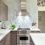 Blue floral wallpaper idea for kitchen backsplash L shaped kitchen counter with white surface and built in sink and faucet a gas stove a kitchen island with white surface and storage at the base