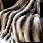 Chinchilla faux fur blanket queen with animal print motif decorated on sofa in living room