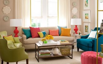 Colorful pillows in various sizes  a white sofa and two armchairs in blue and green colors a wood coffee table a pink round ottoman chair a pair of white round side tables with table lamps