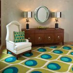 Cool Global View Area Rug In Multiple Tone Colors A White Corner Chair With A Beautiful Throw Pillow A Wood Credenza With Metal Handles An Oval Mirror With Nickel Frame A Pair Of Table Lamps