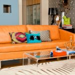 Cool orange leather sofa with colorful pillows a glass top coffee table with metal frame and base an area rug with modern pattern