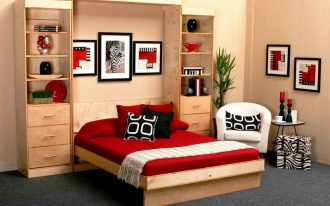 Cozy folded bed furniture integrated with large wooden storage unit red bedding red pillows black pillow monochrome pillows a white corner chair an ottoman with black and white pattern