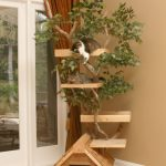 Creative-and-nice-cat-tree-house-with-house-design-and-trees-in-the-corner-near-beige-wall-and-soft-beige-floor-and-near-door
