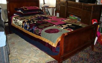 Dark brown stained wood single sleigh bed which is made from cherry wood