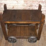 Dark hardwood bar cart with bigger wheels in rustic style