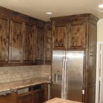 Darker brown wall tall and base kitchen cabinet system in distressed appearance