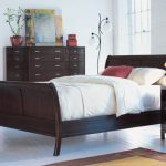 Darker stained wood cherry sleigh bed frame with white bedding and pillows dark stained wood bedside table dark stained wood credenza furniture