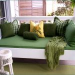 Deep green outdoor daybed mattress idea with green throw pillows and a yellow pillow as the focal point