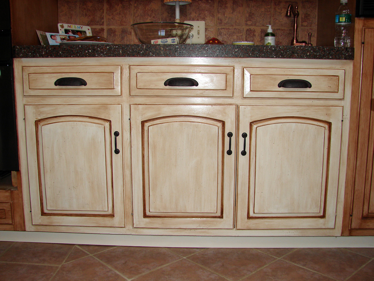 Creating distressed wood cabinets only with paint and wax for Painted cabinets in kitchen