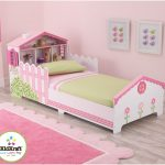 Dollhouse-toddler-bed-by-kidkraft-with-wood-construction-and-painted-finishing-and-bookshelf-headboard-surrounded-with-pink-color
